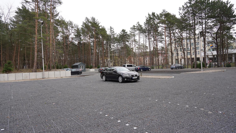 Samochód stojący na parkingu z wieloma wolnymi miejscami.