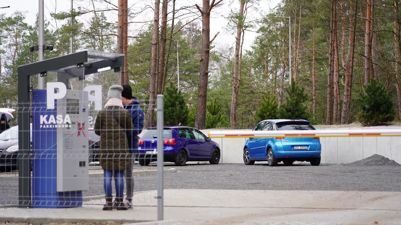 Dwie osoby płacące w parkomacie za postój.